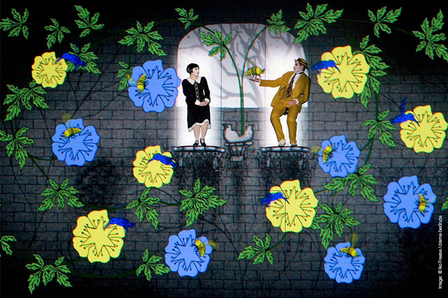 A lady and a man stand on a balcony each while blue and yellow flowers fall around them