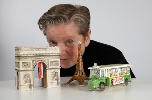 Image of Robyn Archer peering out from behind models of the Arc de Triomphe, the Eiffel Tower and a bus.